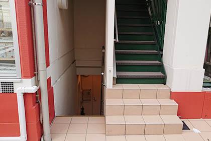 ⑧ 建物の横側から地下へ進み、ドアを開けてお入りください